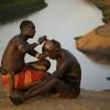 Kara elder making the hair bun on a warrior, Omo Valley, Ethiopia