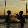 Kara children splashing in the flood waters, Omo Valley, Ethiopia