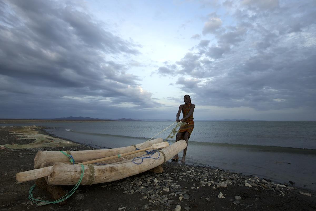Fisherman pulling his boat into Lake Turkana, Northern Kenya